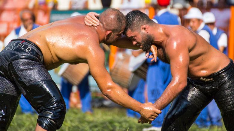 Oil wrestlers grappling