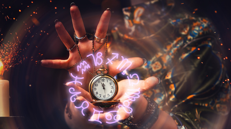 Hands holding watch with astrological symbols around