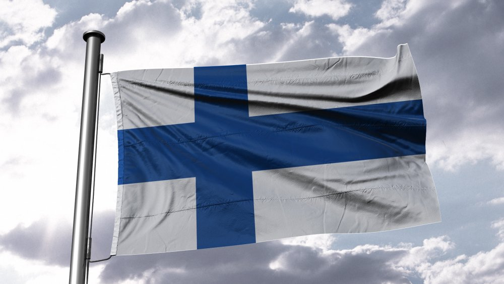 The Finnish flag flaps in the breeze of a blue sky