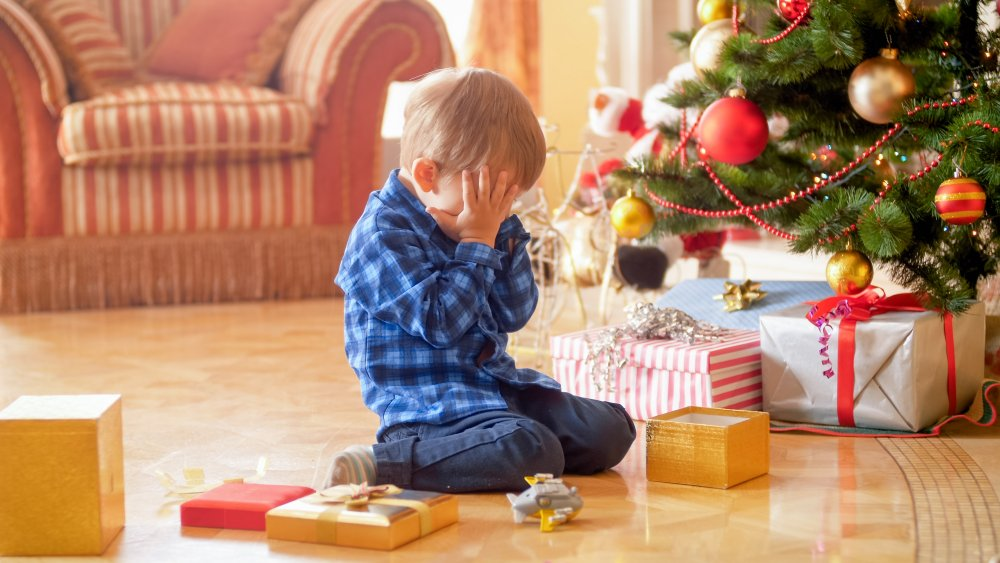 Little boy crying under Christmas tree