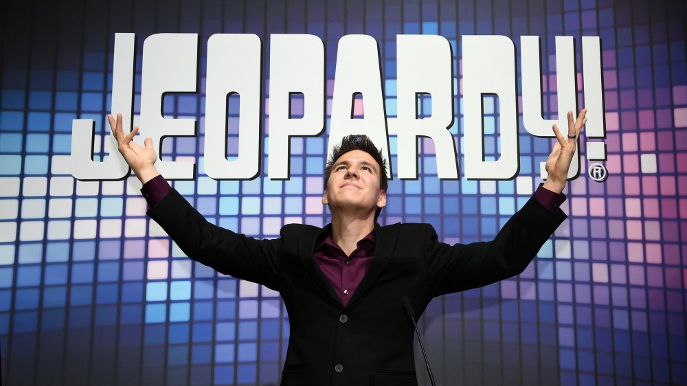 A photograph of James Holzhauer in front of the Jeopardy! logo.