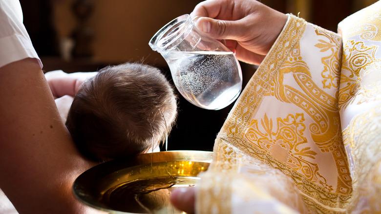 catholic priest baptizes an infant