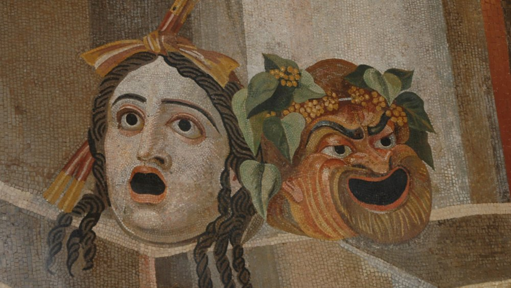 A photograph of ancient tiles depicting a laughing and fearful face.