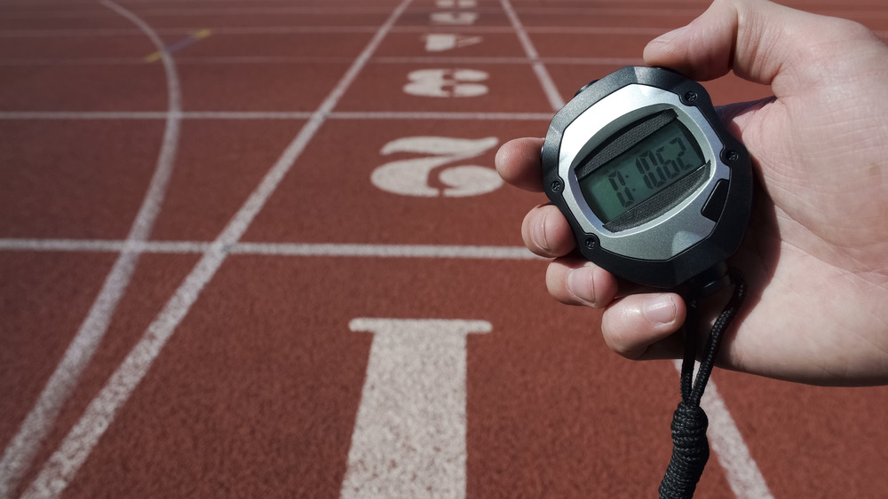 hand holding stopwatch on track