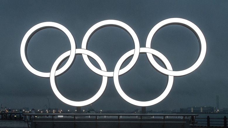 Olympic rings with city behind