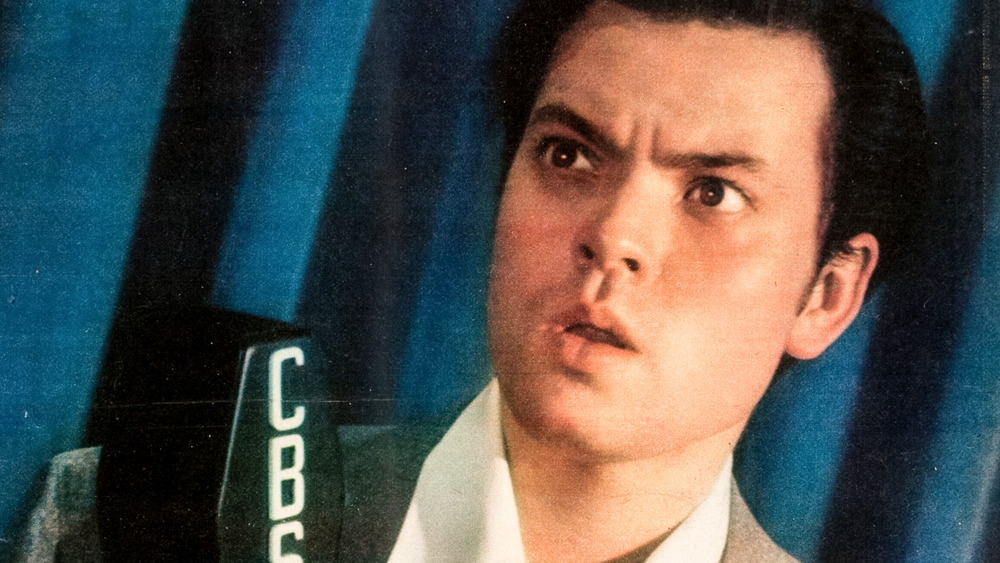 Color portrait photograph of Orson Welles on the cover of the New York Sunday News, recreating the CBS Radio studio in the newspaper's photographic studio in 1938