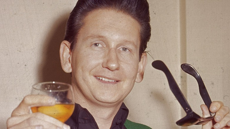Roy Orbison holding sunglasses and a drink