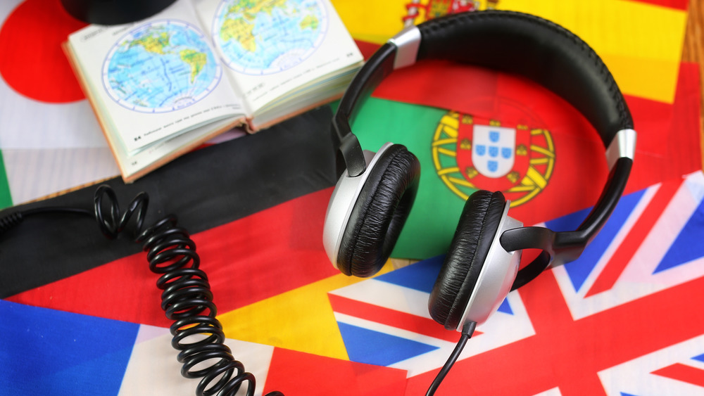 A photograph of headphones on top of a variety of world flags.
