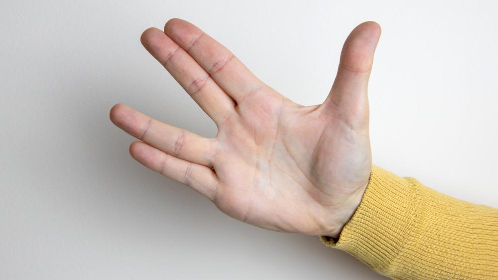 Hand in yellow sweater giving Vulcan salute