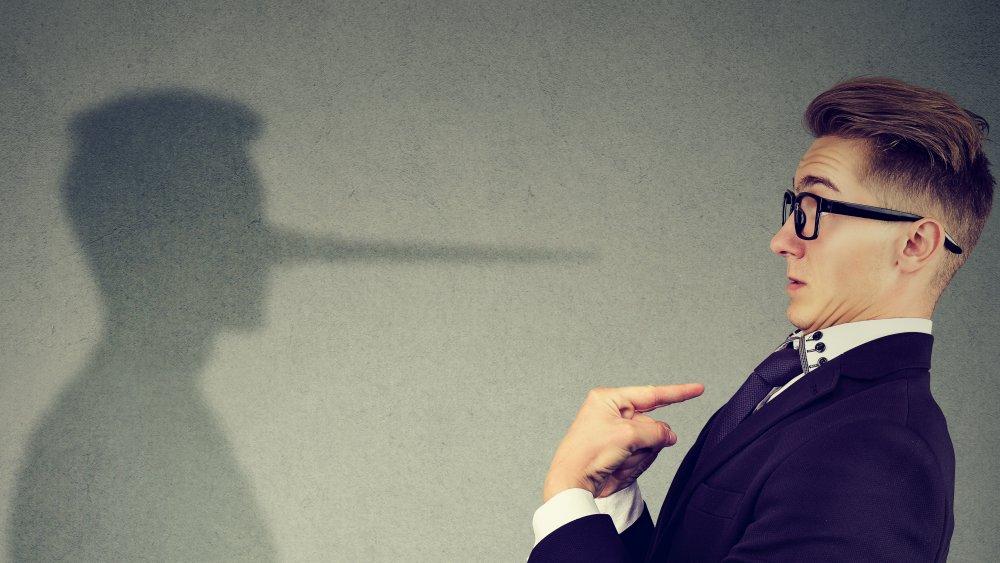 A man with a shadow exhibiting a Pinocchio nose.