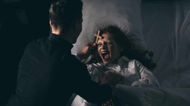 Exorcist with bible and cross over girl in bed