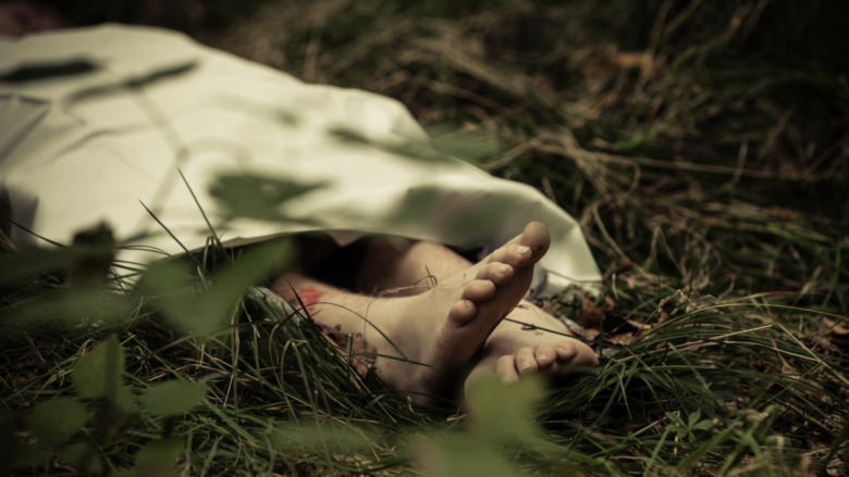 feet poking out of sheet in grass