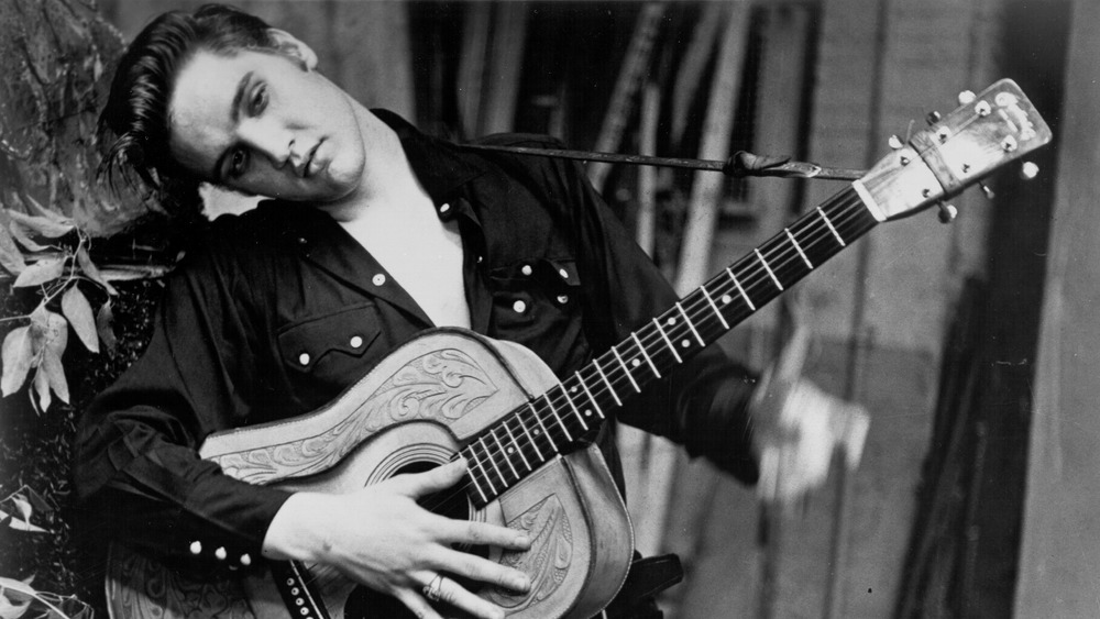 Elvis Presley poses for a portrait tilting his head to the side with guitar in hand