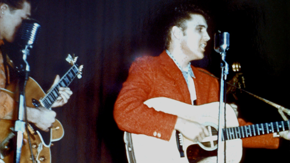 Elvis in a red blazer playing guitar and singing into a mic stand at a high school performance