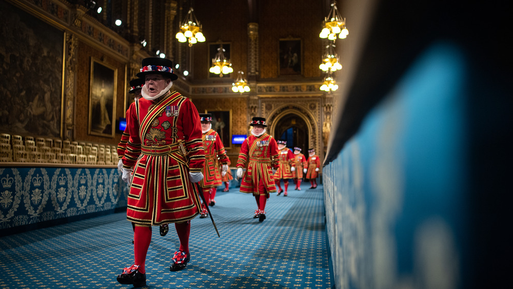 beefeater in tudor dress walking down hall