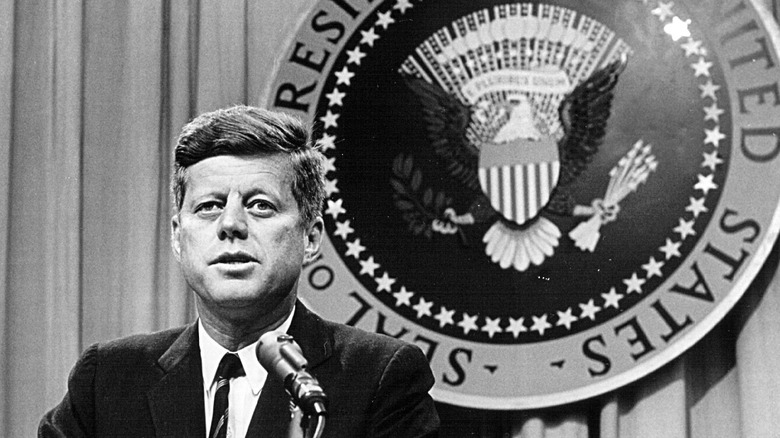 John F. Kennedy in front of presidential seal