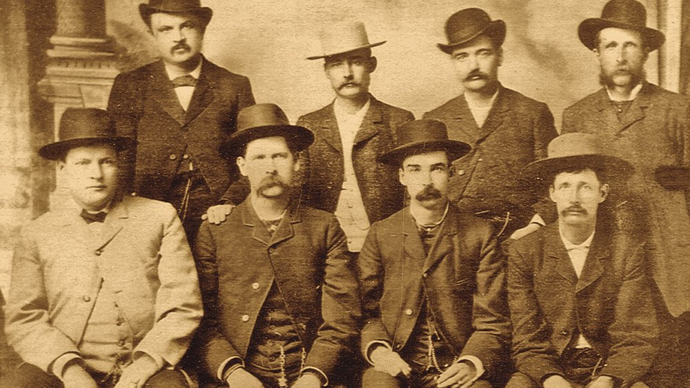 """Dodge City Peace Commission, early June, 1883. From left to right, standing: W.H. Harris, Luke Short, Bat Masterson, W.F. Petillon. Seated: Charlie Bassett, Wyatt Earp, Frank McLain (possibly """"M. C. Clark""""), and Neal Brown"""