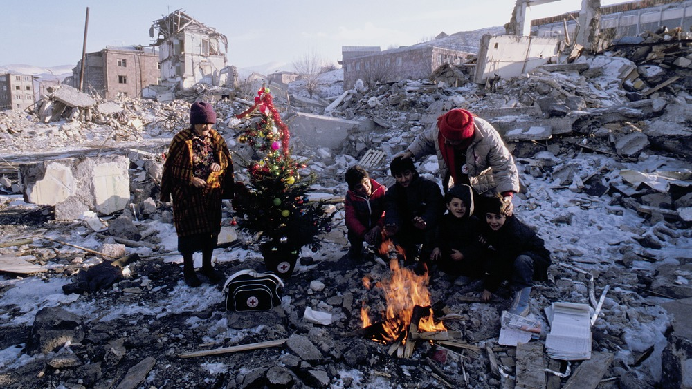 Pictured: family in ruins with Christmas tree at open fire.