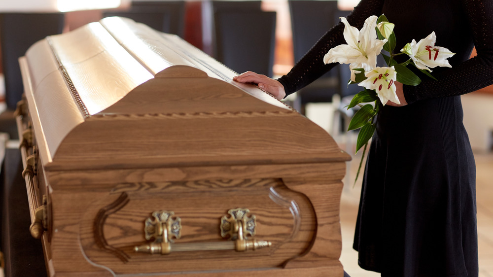 Casket and person with flowers