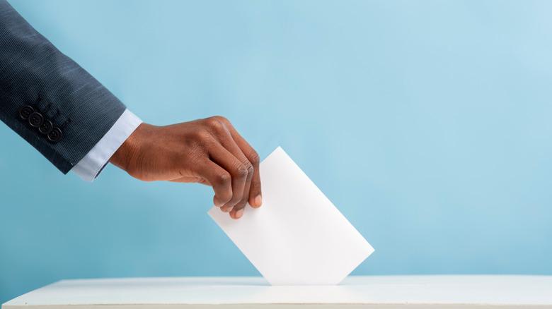 putting a ballot into box