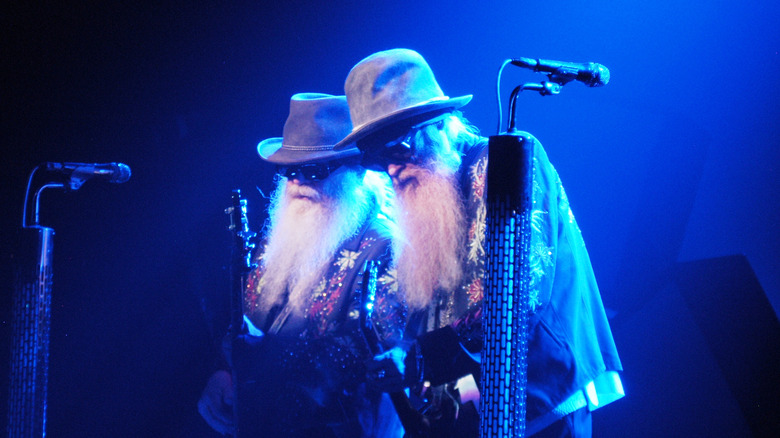 ZZ Top's Billy Gibbons and Dusty Hill stand in a blue light on stage.