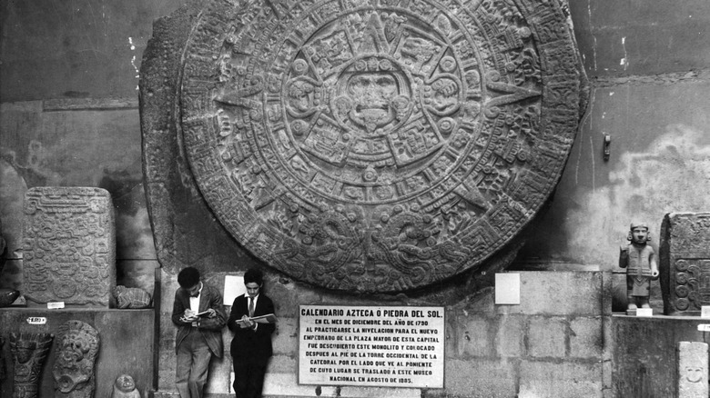 people standing in front of the Aztec Sun Stone