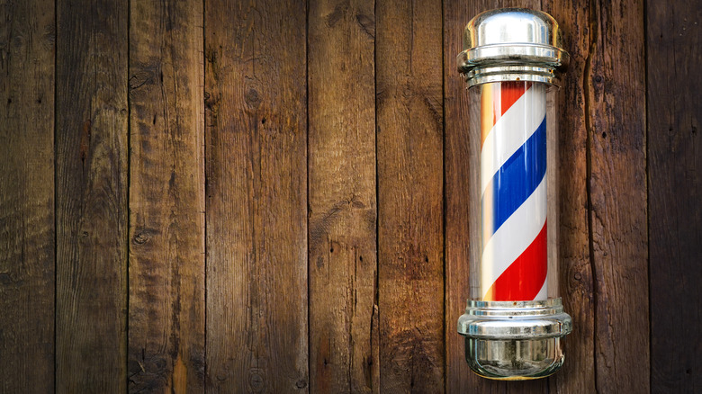 Barber pole on right side against wooden background