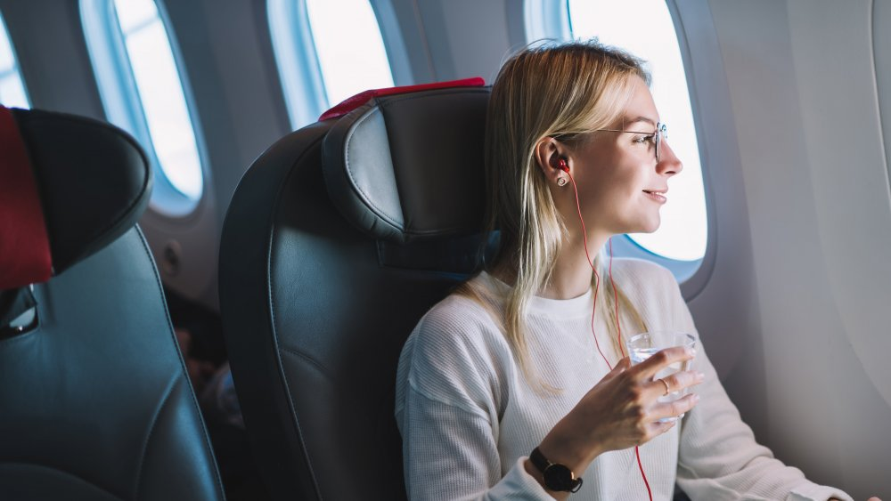 Woman drinking water while sitting on an airplane
