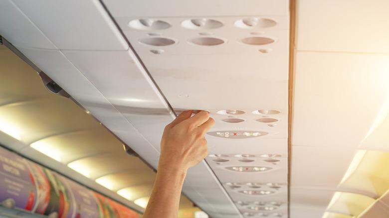 Hand adjusting overhead vent on airplane